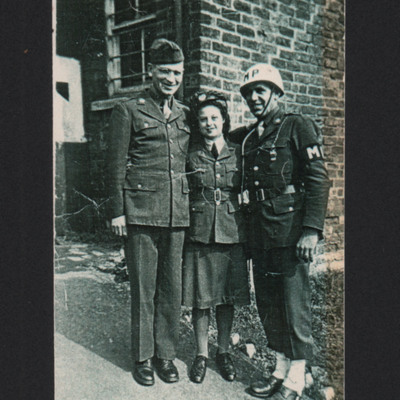 Two men and woman in front of a brick building