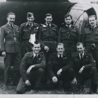 Eight aircrew in front of the rear turret of a Stirling