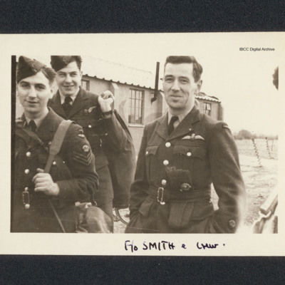 Three aircrew in front of hut