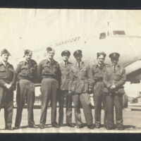 Seven personnel in front of an aircraft