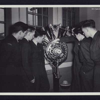Six airmen studying a rotary engine cut-away