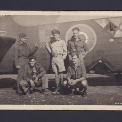 Five airmen by a Wellington