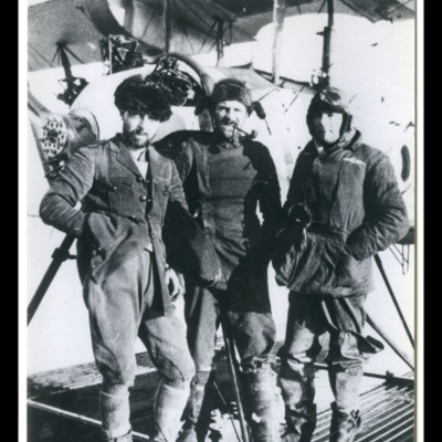 Three men in standing on the float of a seaplane