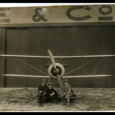 Three men sitting in front of an Avro Antarctic