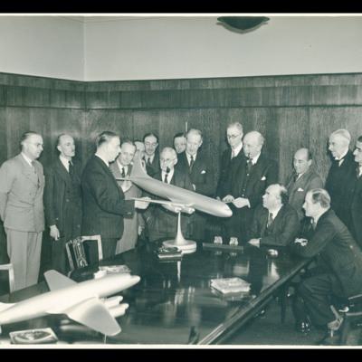 Group of men gathered round a table with two models of aircraft