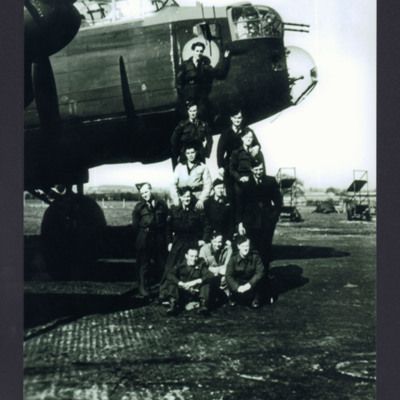 Twelve air and ground crew by a Lancaster
