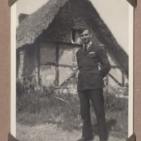 Arthur Atkins in front of a thatched building