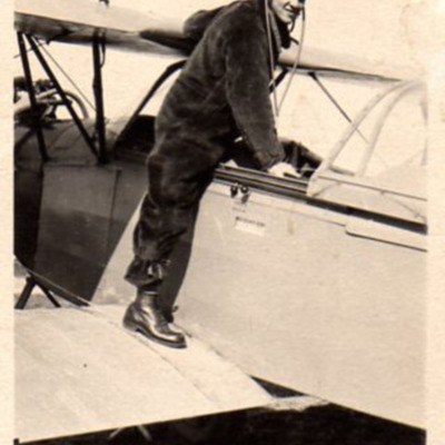 Man standing by cockpit of a bi-plane trainer