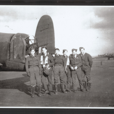 Six aircrew by the tail of a Lancaster