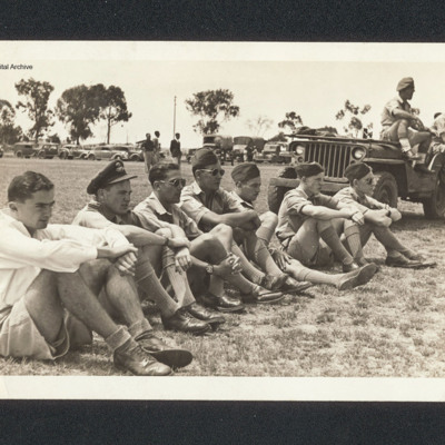 Seven airmen sitting on the grass
