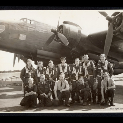 Seven aircrew and five ground crew in front of a Halifax.