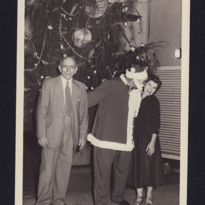 Man and woman with man in father Christmas outfit in front of a tree