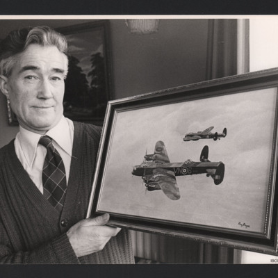 Reg Payne holding painting of two Lancasters