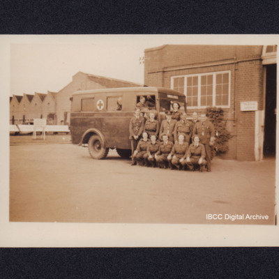 Seven members of Women's Auxiliary Air Force and six airmen in front of an ambulance