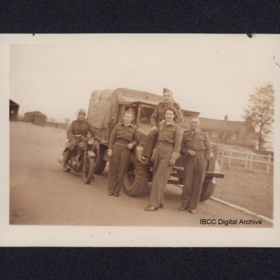 Two members of Women's Auxiliary Air Force and two airmen in front of a lorry and an man on a motorbike