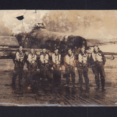 Seven aircrew standing behind a Lancaster