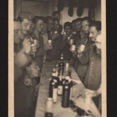 Uniformed men drinking together.