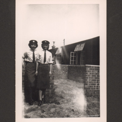 Two members of the Woman's Auxiliary Air Force standing by a brick wall